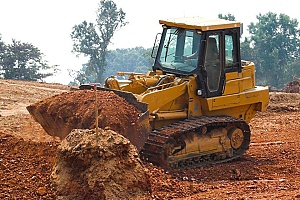 a bulldozer carrying fill dirt for a project