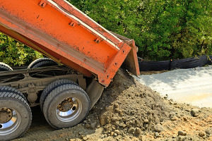 dump truck pouring an exact amount of fill dirt