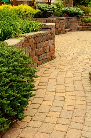 Combination of a retaining wall and landscaping that prevents flooding property