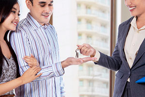 Property manager handing keys to qualified tenants for rental