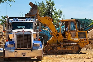 a fill dirt carrier being loaded with many yards of dirt