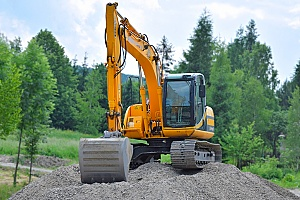 an excavator that is lifting several cubic yards of dirt