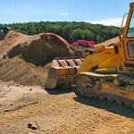 bulldozer moving dirt and preparing it for a delivery
