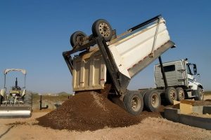 dump truck pouring out fill dirt as part of a Fairfax, VA fill dirt delivery