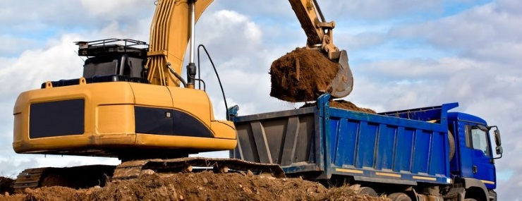an excavator gearing up a blue dirt carrier for a huge Frederick, MD fill dirt delivery