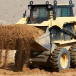 bobcat lifting fill dirt to be transported to a delivery truck in Potomac, MD