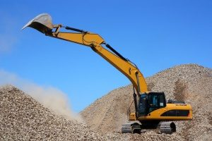 excavator at a Frederick, MD construction site using fill dirt to create a solid building foundation