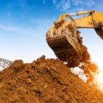 excavator digging up fill dirt form a pile in a Virginia construction site