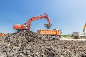 excavator loeading dirt into a dump truck operated by a fill dirt contractor