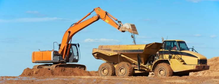 excavator preparing a dump truck for a big Oxon Hill, MD fill dirt delivery to a commercial site