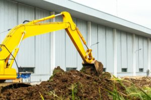 neon yellow excavator digging up free fill dirt in Gaithersburg after a free site inspection and fill dirt delivery by Dirt Connections
