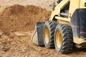 small and compact bulldozer transporting fill dirt at a Gaithersburg, MD construction site