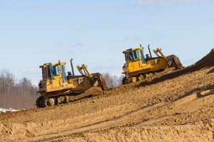two bulldozers in Oxon Hill, MD moving dirt in a commercial forest area