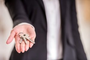 woman who provides Fairfax, VA property manager services holding the keys to a client's house