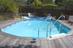 an above ground pool that is built into a deck that will be redone by raising the land around it with fill dirt