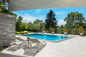beautiful backyard with an inground swimming pool built into the patio