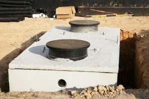 a large septic tank that is being buried into the ground courtesy of a professional Maryland fill dirt contractor