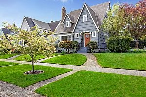 a nicely landscaped front yard of a house with fill dirt that builds up to the house like a hill so that the house can be properly drained of any water runoff so that there is no house flooding