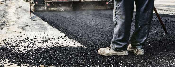 Worker standing on asphalt millings