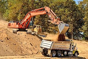an excavator loading up a dirt carrier for any online fill dirt ordering needs around the area of Maryland by homeowners and business owners