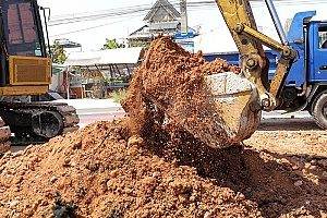 an excavator digging up a pile of fill dirt that will be transported to a comercial construction site to begin building a project foundation