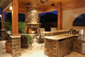 Outdoor patio kitchen with fireplace dining area
