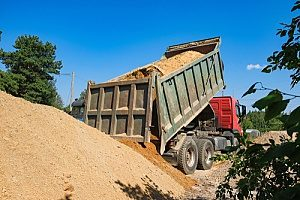 a dirt carrier truck transporting Virginia fill dirt to a homeowner who is looking to stabilize their yard