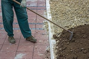a man laying topsoil in his yard after a Virginia fill dirt contractor placed a layer of fill dirt where there is no grass
