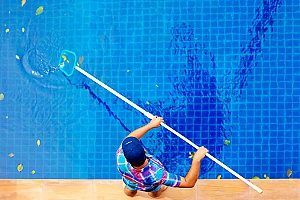 a man using a net to clean an unused pool and is therefore wasting time and money versus choosing pool removal services