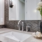 a new sink in a bathroom remodel that is equipped with a very modern backsplash