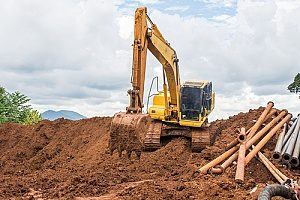 an excavator working with fill dirt to level out a site that was approved to operate on after a safety inspection