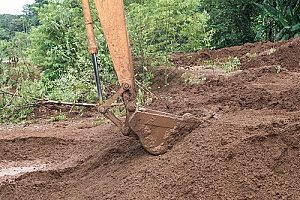 excavator digging up clean fill dirt provided by a Virginia fill dirt contractor so the project can be ready to be built