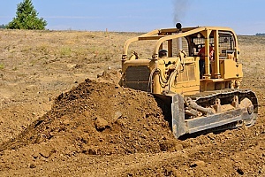 a bulldozer scooping up clean fill dirt before loading it into a dirt carrier for transportation