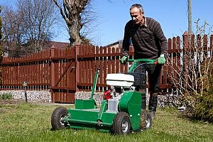 a man aerating his lawn in preparation of the snow as well as his fill dirt project that he will receive the help of a Virginia fill dirt contractor for