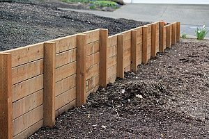 a retaining wall that is built on fill dirt to keep plants upright and healthy while also protecting the yard