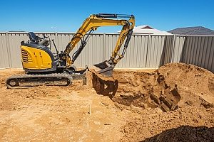 an excavator conducting land grading in a backyard to fix landscaping issues using fill dirt