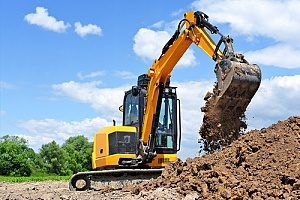 an excavator digging up fill dirt for a commercial project that requires excavation and land grading