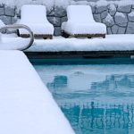an inground swimming pool surrounded by snow that must be drained in order to receive Fairfax, VA pool removal services