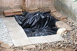 a backyard pond that is being built and has pond liner on it