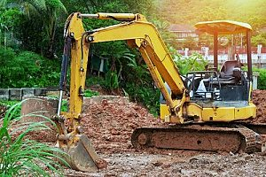 a pool removal contractor using an excavator to fill a backyard with fill dirt