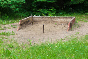 a horseshoe pit built in a sandbox area in a backyard