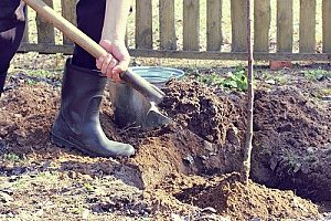 a man using a shovel to replace an area he dug up with fill dirt