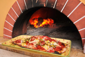 a pizza on a colorful plate that was baked in an outdoor pizza oven