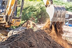 an excavator removing excess dirt from a construction site after the project