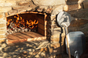 an outdoor pizza oven burning wood with a pizza peel next to it
