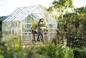 woman in her backyard greenhouse