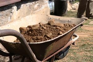 dirt in a wheelbarrow around a foundation