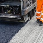 asphalt millings being laid on a road by contractors