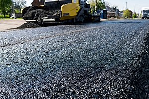 asphalt millings being spread across a road