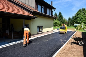 men working on asphalt millings for a home